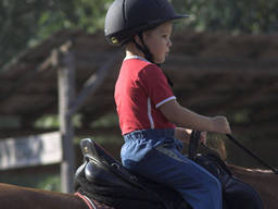 A kid learning how to ride a horse