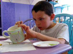 A young boy shows full attention as he paints his ceramic mug.