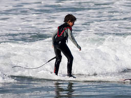 A young boy in full gear surfs near the shore.