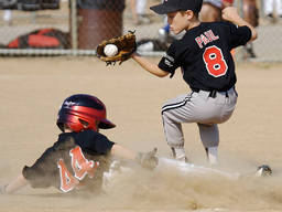 A young boy hits the base safely just as the ball is caught by the opposing player.