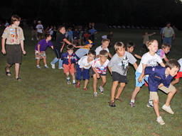 Cub scouts participate in various physical activities, such as a cooperation relay, to promote teamwork and self-reliance.