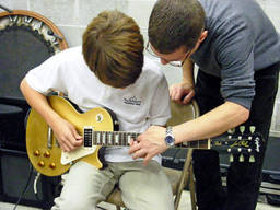 A kid being taught by his teacher to play guitar