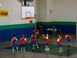 Kindergarten boys and girls score some shots at a basketball camp