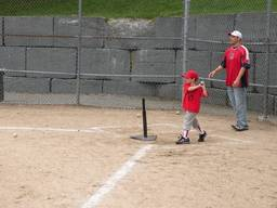 Father and child practice t-ball