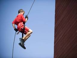 Young boy abseiling from a cliff