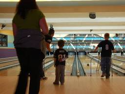 Kids playing ten pin bowling with their parents