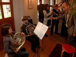 Children playing a piece from a score using a French horn