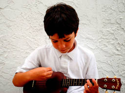 This kid loves strumming his ukulele