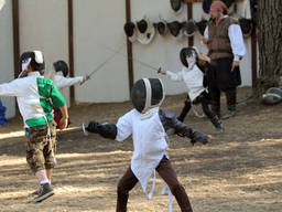 A kid happily showing his fencing skills
