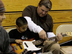 Young boy learning the basics of bass guitar playing