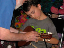 Bouzouki instructor teaching a child how to play the instrument properly.