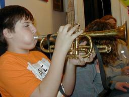A young boy blowing air into a cornet