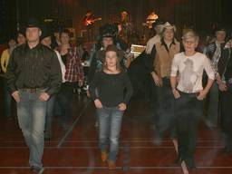 Children and adults learning country dancing together