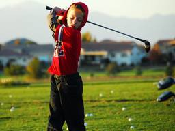 Young boy swinging his golf club.