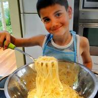 A kid learning how to cook pasta